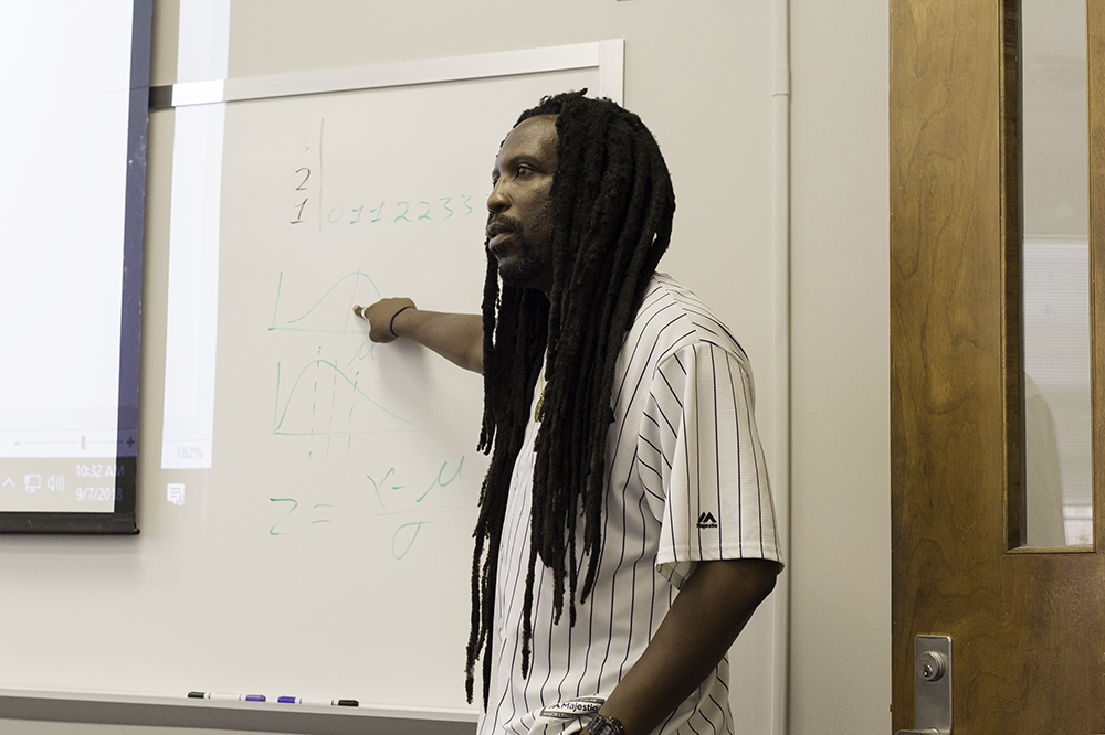 A professor stands before his class, gesturing toward a whiteboard and projector screen.