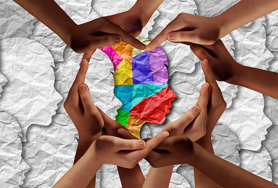 Hands of many colors form the shape of a heart around an illustration of a multi-colored human head.